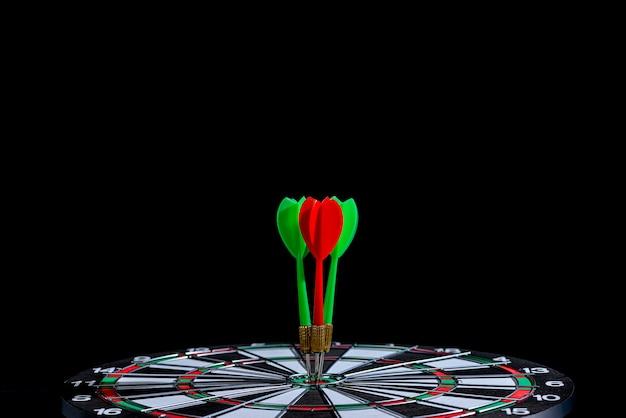 Seta de dardo vermelho e verde, atingindo o centro do alvo