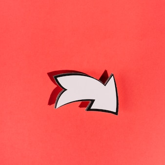 Seta direcional branca sobre fundo vermelho