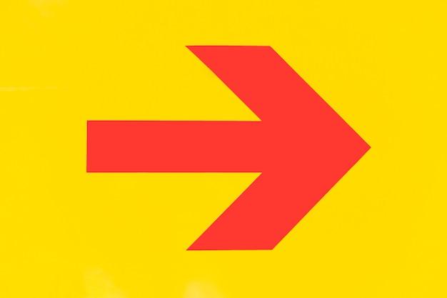 Seta pontuda vermelha em fundo amarelo