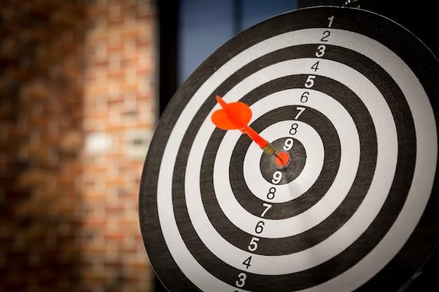 Seta vermelha do alvo do dardo que bate no bullseye com, mercado de alvo.
