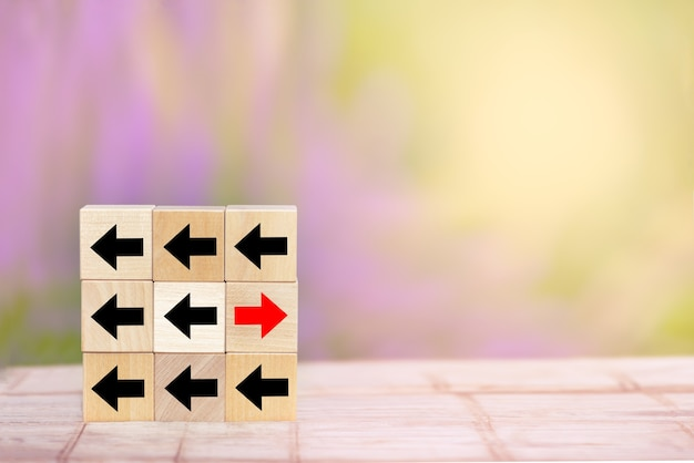 Seta vermelha do bloco de madeira apontando para o lado oposto, perturbadora das setas pretas na mesa de madeira.