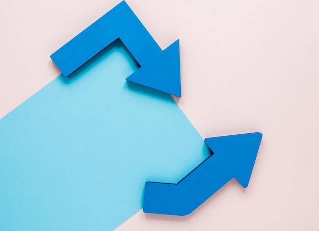 Setas azuis de vista superior e maquete de papelão azul sobre fundo rosa