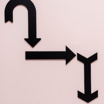 Setas pretas planas leigos em fundo rosa