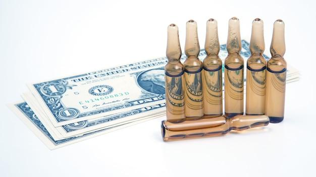 Sete ampolas de vidro médicas para injeção no fundo das notas de dólar. negócios e farmácia