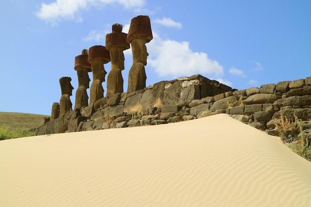Sete estátuas moai de ahu nau nau cercadas por areia de coral mole da praia de anakena, ilha de páscoa, chile