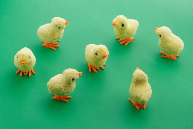 Sete galinhas de brinquedo amarelo sobre um fundo verde.