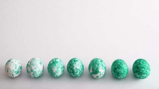 Sete ovos de páscoa com padrão verde e efeito gradiente em linha no fundo branco com espaço de cópia