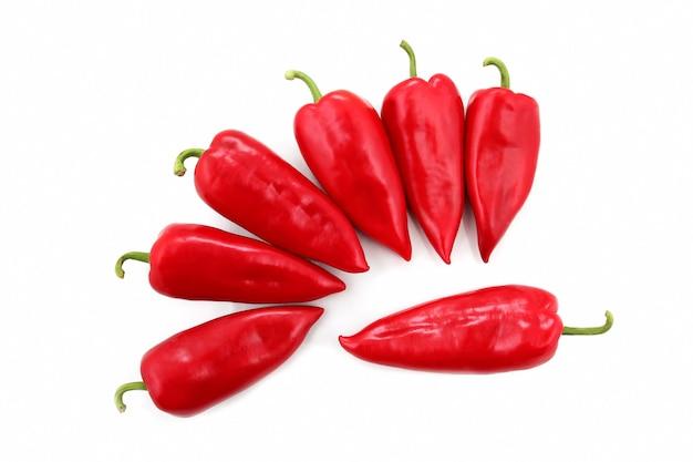 Sete pimentões vermelhos brilhantes em um fundo branco