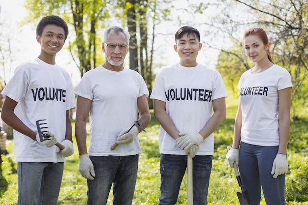 Setor de meio ambiente. energéticos quatro voluntários em pé e segurando ferramentas de jardim
