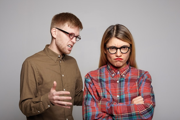 Seu casal europeu discutindo: barbudo de óculos ovais tentando convencer a teimosa namorada que cruza os braços e faz uma careta de descontentamento, expressando desacordo