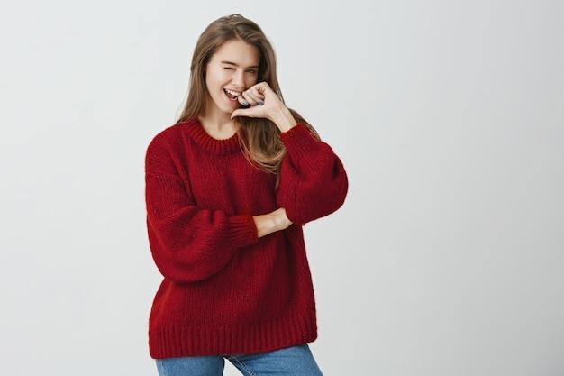 Seu coração tremerá de mim. menina europeia encantadora emotiva na camisola vermelha solta piscando e flertando, sorrindo amplamente, segurando a mão no queixo em pé.
