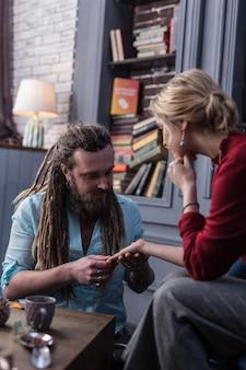 Seu futuro. homem simpático e alegre sorrindo enquanto lê a palma da mão de seu cliente