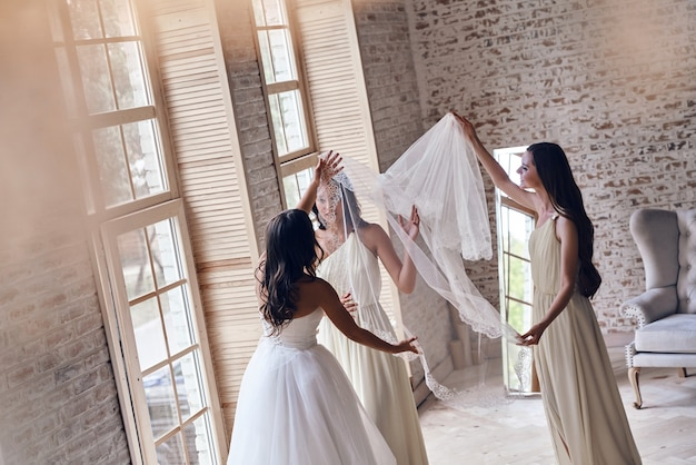 Seu maior dia. damas de honra ajudando a noiva a colocar um véu enquanto estão juntas perto da janela