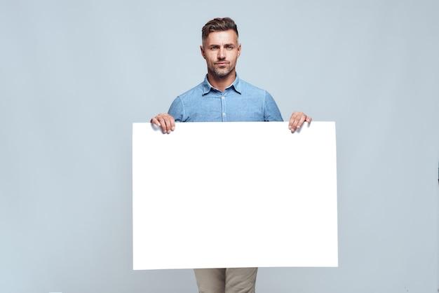 Seu texto aqui. retrato de homem barbudo bonito em roupas casuais, segurando o tabuleiro em branco vazio e olhando para a câmera em pé contra um fundo cinza. propaganda
