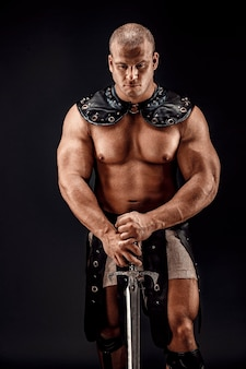 Severo bárbaro em traje de couro com espada. retrato de gladiador musculoso careca.