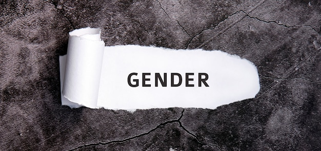 Sexo com papel branco rasgado em uma mesa de concreto cinza.