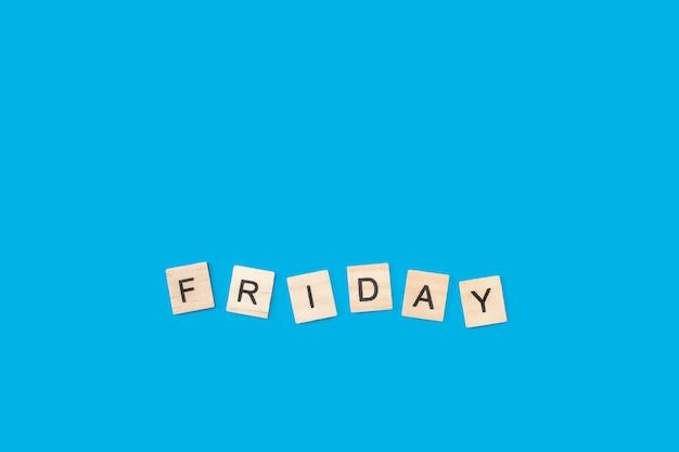 Sexta-feira, escreva com cubos de letras de madeira em um fundo azul