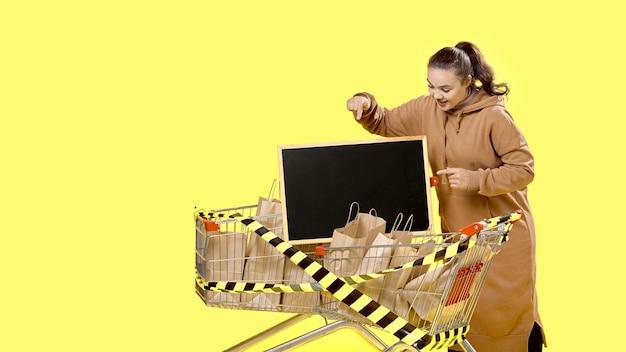 Sexta-feira negra, a garota aponta para uma placa na cesta de compras