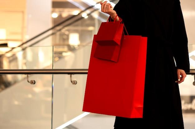 Sexta-feira negra, mulher segurando uma sacola de compras vermelha no fundo do shopping