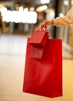 Sexta-feira negra, mulher segurando uma sacola vermelha de compras em pé no fundo do shopping