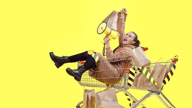 Sexta-feira negra, uma menina está sentada em uma cesta de compras e grita alegremente em um megafone