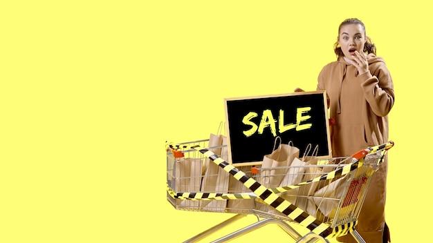 Sexta-feira negra, uma menina olha para a câmera surpresa, ao lado de uma placa em uma cesta de compras