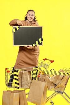 Sexta-feira preta. a garota aponta para uma placa preta com um lugar para copiar, parada em um carrinho de compras.