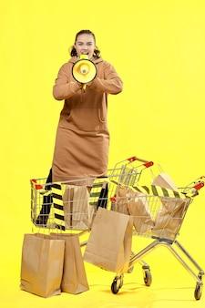 Sexta-feira preta. a garota grita em um megafone, parada entre os pacotes no carrinho de compras.