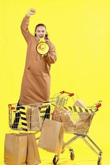 Sexta-feira preta. a garota grita no megafone, levantando uma das mãos, parada entre os pacotes no carrinho de compras.