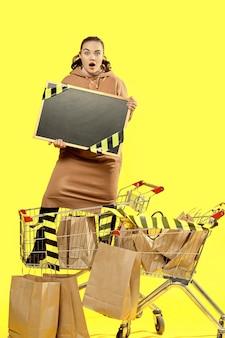 Sexta-feira preta. a menina chocada mostra uma placa com um local para copiar, em pé na cesta de compras.