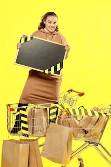 Sexta-feira preta. a menina mostra uma placa com um lugar para copiar, de pé em um carrinho de compras.