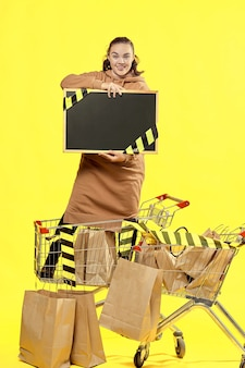 Sexta-feira preta. a menina segura uma placa preta, com um lugar para copiar, em um carrinho de compras.