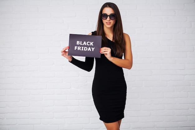 Sexta-feira preta. mulher com a inscrição black friday e sacos de presente