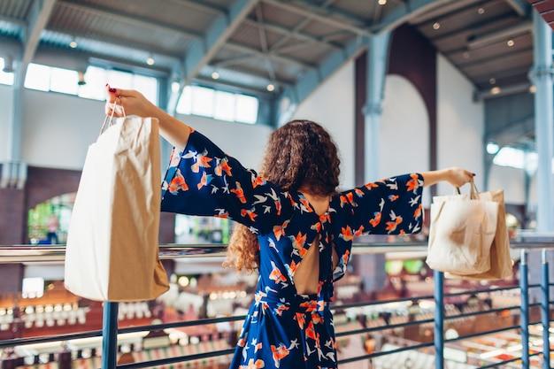 Sexta-feira preta. mulher feliz que levanta as mãos com os sacos de papel de compra no shopping.