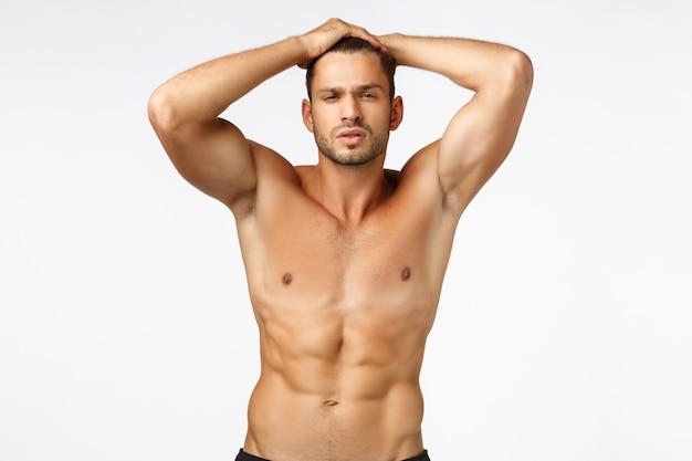 Sexy bonito, bronzeado masculino jovem mostrando seu corpo perfeito, torso nu