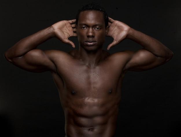 Sexy homem afro-americano com as mãos para a cabeça