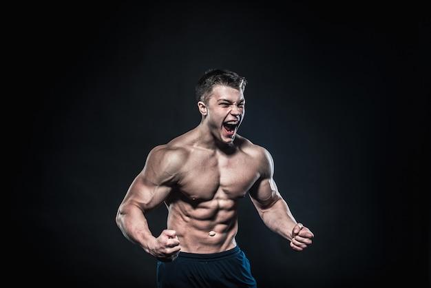 Sexy jovem atleta posando o fitness, musculação