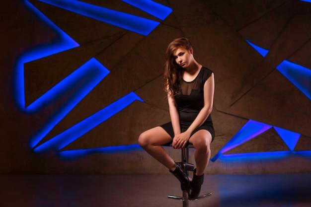 Sexy jovem garota em um vestido preto em um bar fezes