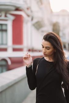 Sexy, jovem mulher no corpo fuma na rua