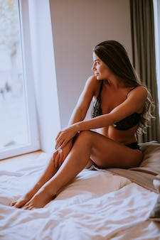 Sexy jovem sentada na cama