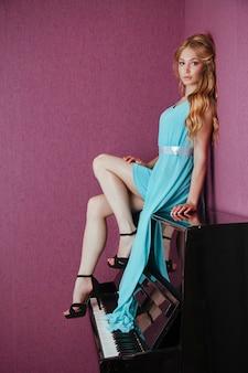 Sexy loira linda num vestido tocando piano