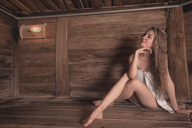 Sexy mulher jovem e bonita sentada na sauna de madeira