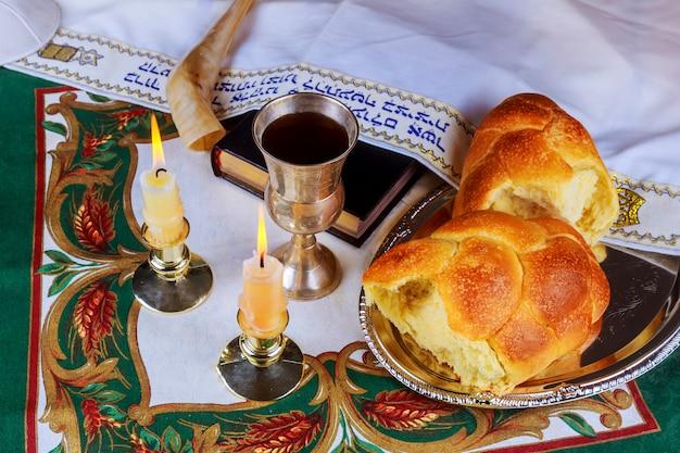 Shabat mesa de véspera com chalá pão, velas e kipá.