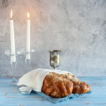 Shabat shalom - pão chalá, vinho do shabat e velas na mesa de madeira
