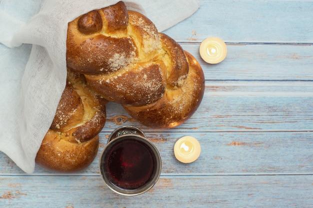 Shabat shalom - pão chalá, vinho do shabat e velas sobre fundo azul de madeira. vista do topo. copie o espaço