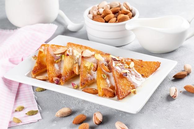 Shahi tukra / tukda ou double ka meetha é um pudim de pão doce indiano de fatias de pão frito embebido em leite com raiva ou doce de açafrão guarnecido com frutas secas, foco seletivo