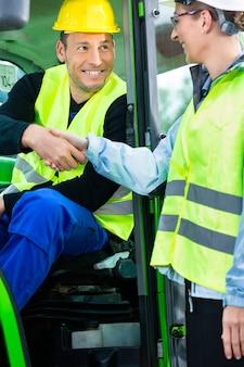 Shake de mão de trabalhador de construção com o engenheiro no canteiro de obras