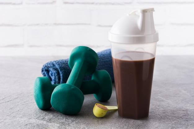 Shake de proteína de chocolate e halteres em pedra cinza