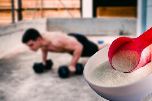 Shake de proteína sabor baunilha acompanhado por pesos e esportistas ao fundo