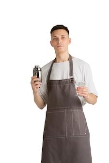 Shaker. retrato de um jovem barista ou barman caucasiano no avental marrom sorrindo. fundo branco do estúdio, copyspace. fazendo coquetéis, convidando convidados. ocupação profissional, bebida, serviço.